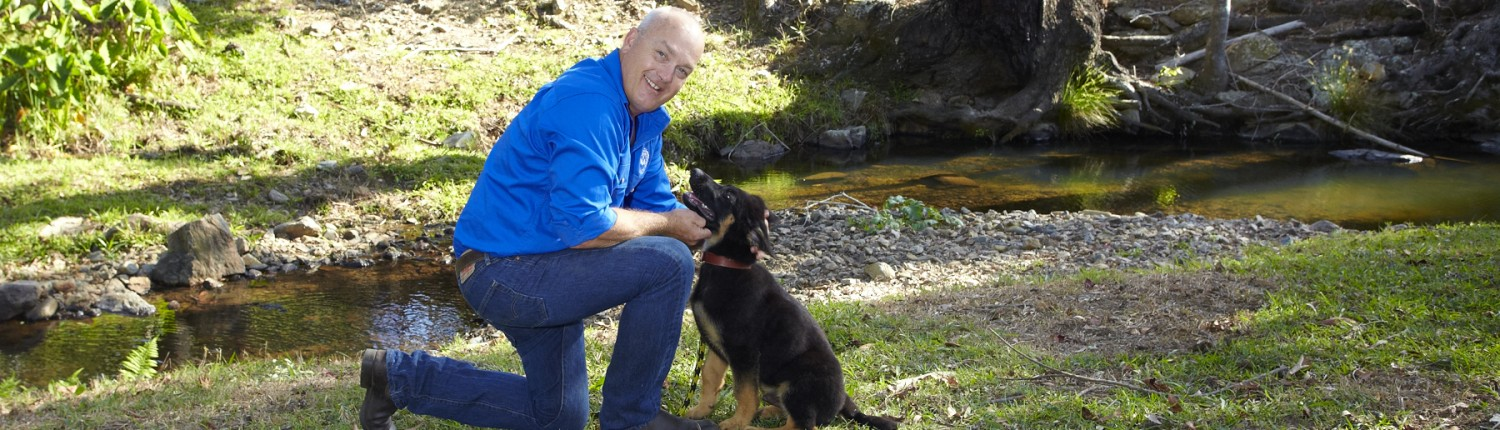 Scott Donald demonstrating his dog training technique by a creek